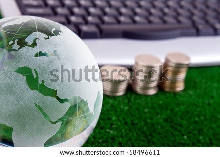 keyboard,coins and glass globe on green grass - stock photo