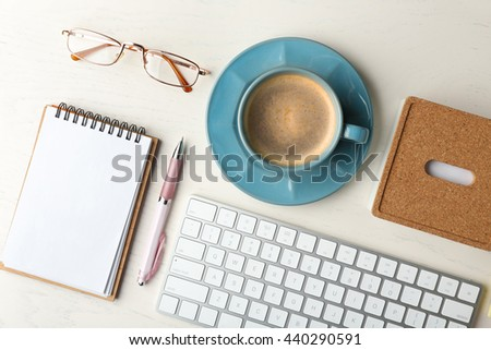 Keyboard, notebook and cup of coffee on a wooden desk background, top view