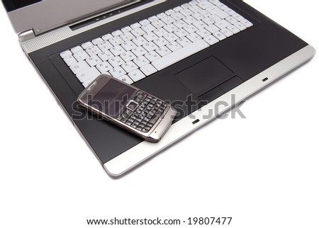 Keyboard of high-end laptop and modern smartphone on it. - stock photo