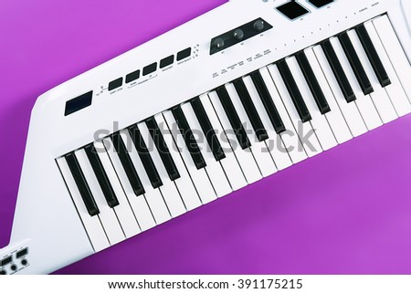 Keyboard of synthesizer on purple background - stock photo