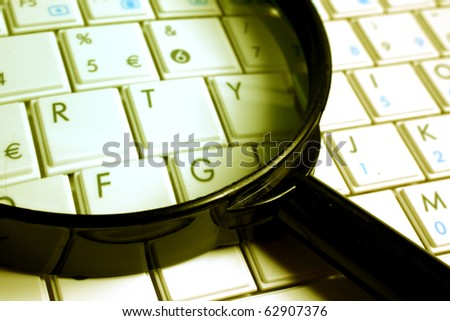 keyboard with a magnifying glass, concept of online security and investigation. - stock photo
