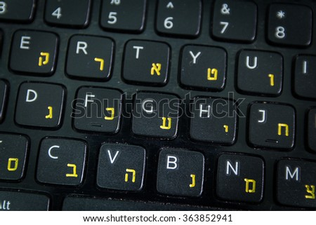Keyboard with letters in Hebrew and English - Laptop keyboard - Top View - Close up - Dark atmosphere