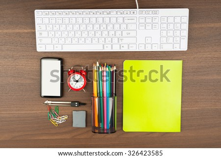 Keyboard with office supplies on wooden table - stock photo