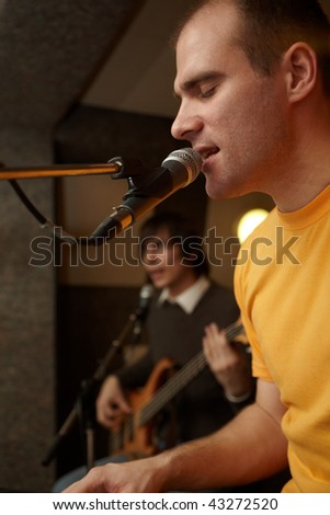 keyboarder is playing and singing. guitar player in out of focus - stock photo