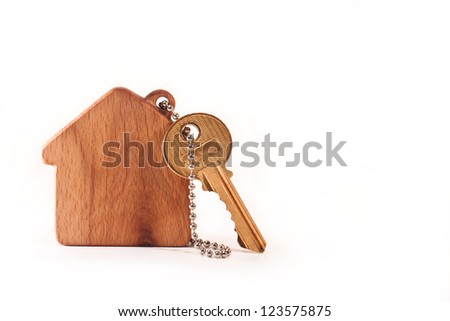 Keychain in the shape of the house with a key on a white background - stock photo
