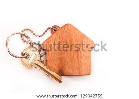 Keychain shaped like a house with a key on a white background - stock photo