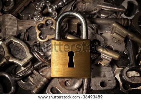 Keyhole on a golden padlock over many old reys - stock photo