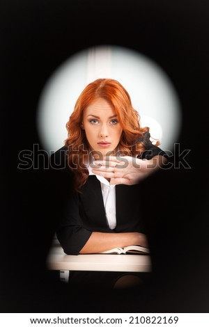 keyhole view of young pretty business woman. red-hair girl working on computer and hiding notes - stock photo