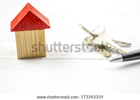 Keys and a pen lying on paperwork alongside a model of a house conceptual of ownership, purchase, selling or insurance and the signing of the contract - stock photo