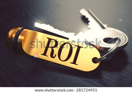 Keys and Golden Keyring with the Word ROI - Return On Investment - over Black Wooden Table with Blur Effect. Toned Image. - stock photo