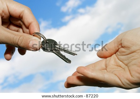 keys being handed over against blue sky - stock photo