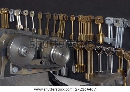 Keys for cutting on a special wall and a part of equipment in a workshop - stock photo