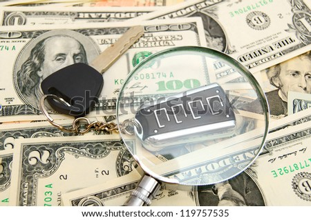 Keys from the car and a magnifier on dollars. - stock photo