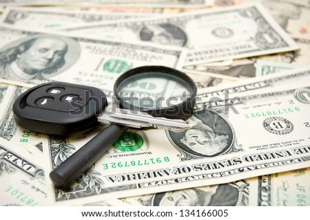 Keys from the car and a magnifier on money. - stock photo