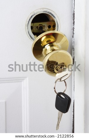Keys hanging from a door knob falling out of the door. - stock photo