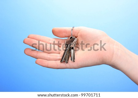 Keys in hand on blue background