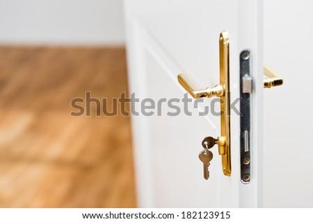Keys in the keyhole with beautiful golden doorknob on white door - stock photo