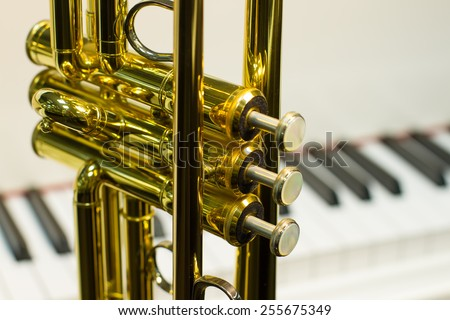 keys of trumpet close up on background piano - stock photo