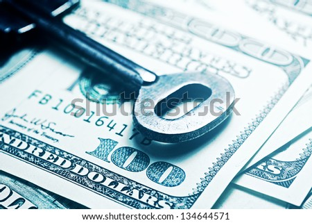 Keys on a one hundred dollar banknote in blue tone. - stock photo