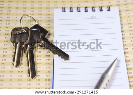 Keys on financial report with pen and notepad for business concept         - stock photo