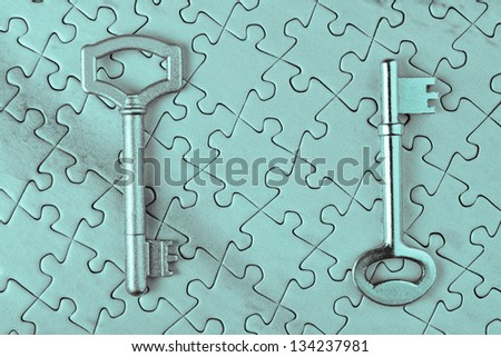 Keys on the puzzle close-up in cold tones. - stock photo