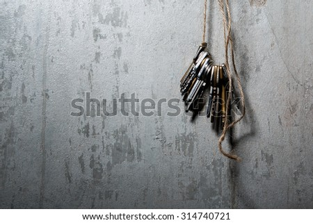 Keys on the thread over concrete wall - stock photo