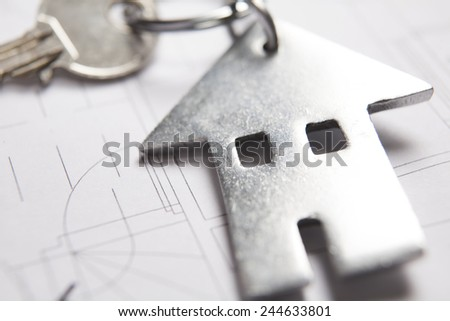 Keys To Home On Architects Plans With House Shaped Keyring - stock photo