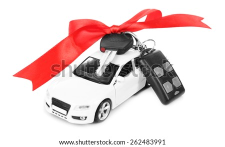 Keys with red bow on car as present isolated on white - stock photo