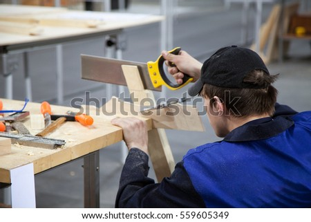 Khabarovsk, Russia - April 24, 2016:Carpenter in a blue uniform working with a saw and wood at the workshop. Young Caucasian man at the workbench with tools
