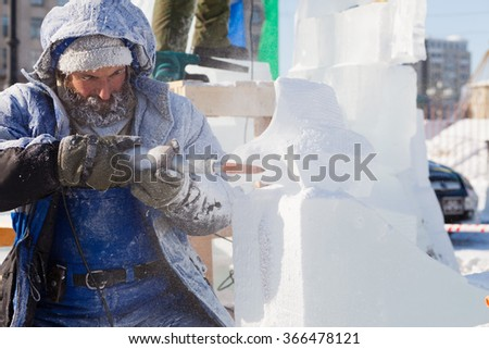 KHABAROVSK, RUSSIA - JANUARY 23,  2016: Sculptor working on ice sculpture