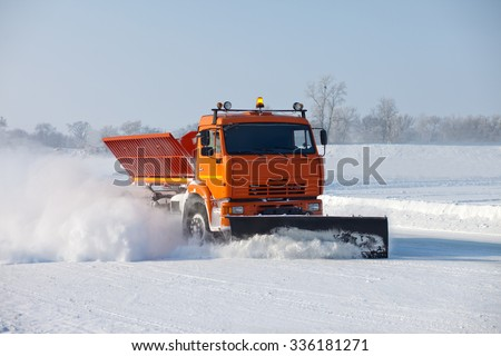 KHABAROVSK, RUSSIA - JANUARY 26, 2015: Snowplow is cleaning a road and snow flying around it