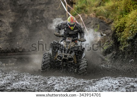"KHABAROVSK RUSSIAN - SEPTEMBER 12 : Fedor Petrov in action at The second stage of the Khabarovsk enduro ""Drive trofy on September 12, 2015 in Khabarovsk RussiaATV rides through the mud with big splash"