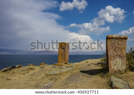 Khachkar (cross stone) on Sevan lake, Armenia. Storm clouds and mountains on background.