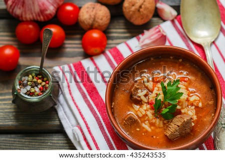 Kharcho soup. Thick beef soup with rice, tomatoes, carrots, peppers, walnuts and spices. A traditional dish of Georgian cuisine - stock photo