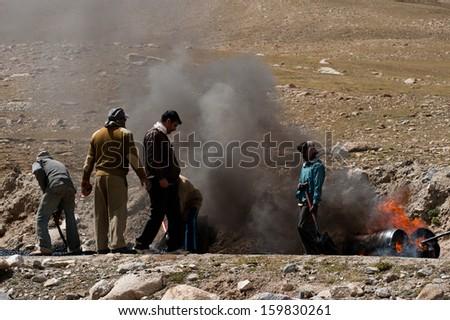 KHARDUNG LA PASS, INDIA - SEPTEMBER 12: Indian people working at road construction at Khardung La pass. The one main road at Himalaya mountains, altitude 5600 m. India, Ladakh, September 12, 2012 - stock photo