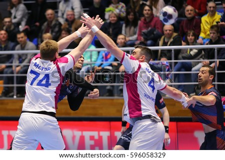 "KHARKIV, UKRAINE - MARCH 4, 2017: TCELISHCHEV Lev and BUINENKO Evgeniy blocking GREBILLE Mathieu. EHF Men's Champions League match HC Motor Zaporozhye vs Montpellier HB, Palace of Sports ""Lokomotiv"""