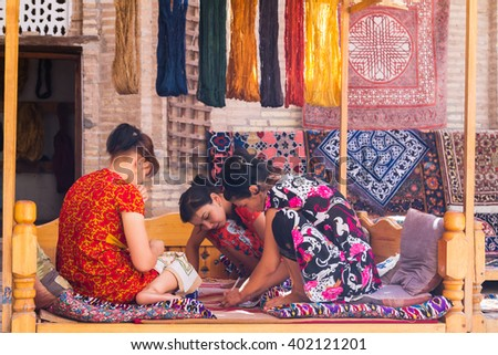 KHIVA, UZBEKISTAN - MARCH 14, 2015: Unidentified female weaver knotting a handmade carpet in Khiva, Uzbekistan, Central Asia. Uzbekistan is popular with hand made carpets.