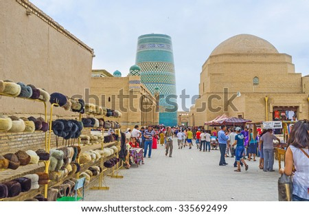 KHIVA, UZBEKISTAN - MAY 3, 2015: The tourist bazaar on the central street with the blue Kalta Minor Minaret on the background, on May 3 in Khiva.