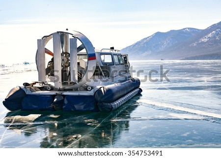 Khivus winter.Transport on ice. Hovercraft. Ice on the surface of the transparent frozen Lake Baikal. floe, crack, snow, reflection. Blue sky.  transparent ice. Horizon. Horizontal. Baikal in winter.  - stock photo