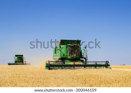 Khmelnitskiy, Ukraine - July 23: Modern John Deere combine harvesting grain in the field near the town Khmelnitskiy, Western Ukraine July 23, 2015 - stock photo