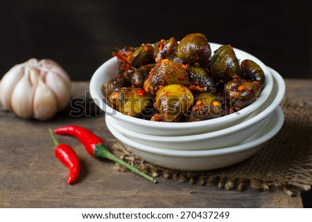 "Khmer style Street food : Small river shells mixed with some chili powder, salt, sugar, glutamate, and ""cooked"" on the sun Khmer call it ""Lee hal"" - stock photo"