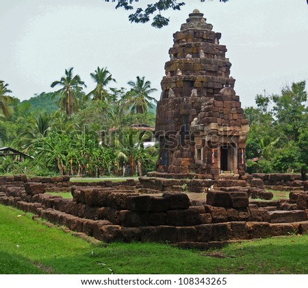 khmer temple in the jungle with coconut trees - thailand - stock photo