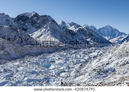 Khumbu glacier near Everest Base Camp, Himalayas, Nepal. Beautiful landscape of a white snowy mountain glacier. Huge glacier in high mountains on a bright sunny day. - stock photo