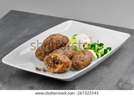 Kibbe with cucumber salad and feta - stock photo