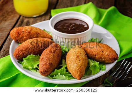 Kibbeh - traditional Arabian meatballs, minsed meat and bulgur or rice wheat fried snack with green salad, ketchup  in white plate on wooden background. Eastern cuisine. Selective focus - stock photo