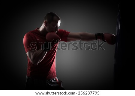 Kick boxer boxing as exercise for the big fight. Boxer hits punching bag. Young boxer trains on punching bag - stock photo