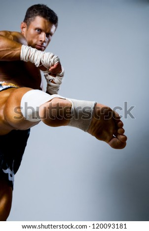 Kick-boxer training before fight on a gray background - stock photo