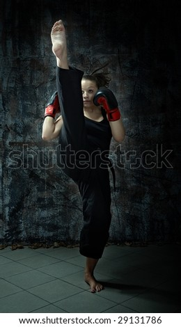 Kick boxing fighting woman wearing boxing gloves - stock photo