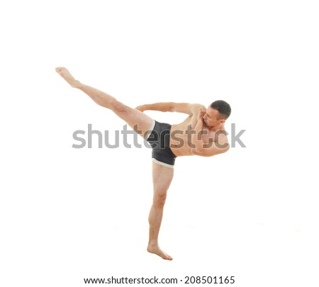 Kick by professional boxer fighter standing in fight position wearing only shorts - stock photo