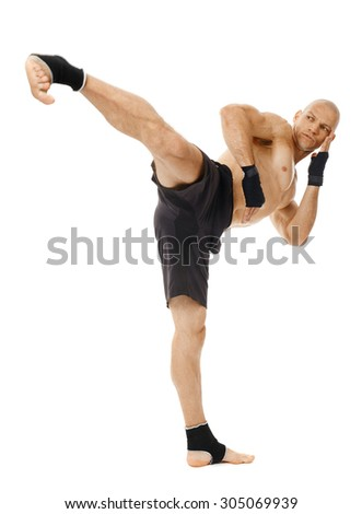 Kickbox or muay thai fighter executing a powerful kick isolated on white background - stock photo